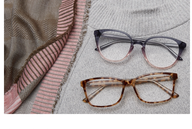 Round acetate glasses #4440112 in translucent gray-and-pink ombre and tortoiseshell rectangle glasses #2023625 folded on top of a light gray cashmere sweater and pink-and-gray scarf.