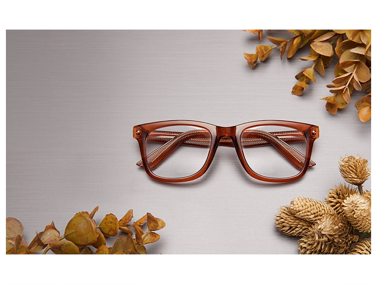 Value-priced square glasses #125215 in translucent brown surrounded by fall foliage on a tabletop.