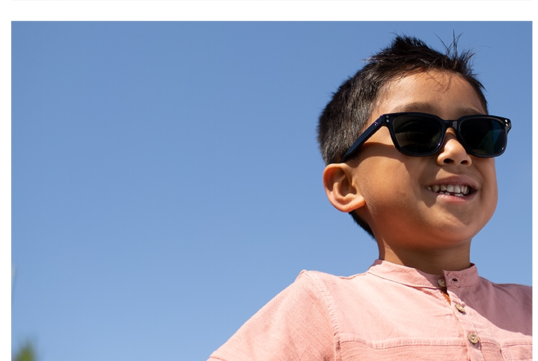 Young boy with short brown hair standing outside wearing Wayfarer-style black acetate sunglasses #4433121 with photochromic lenses and a pink short-sleeve pocket tee.