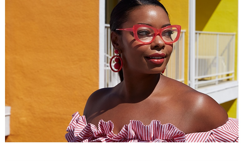 African-American woman with hair pulled back wearing bold candy pink cat-eye glasses #4438119 and off-the-shoulder pink-and-white striped ruffle top standing in front of vibrant yellow-and-orange façade of Saguaro Hotel in Palm Springs.