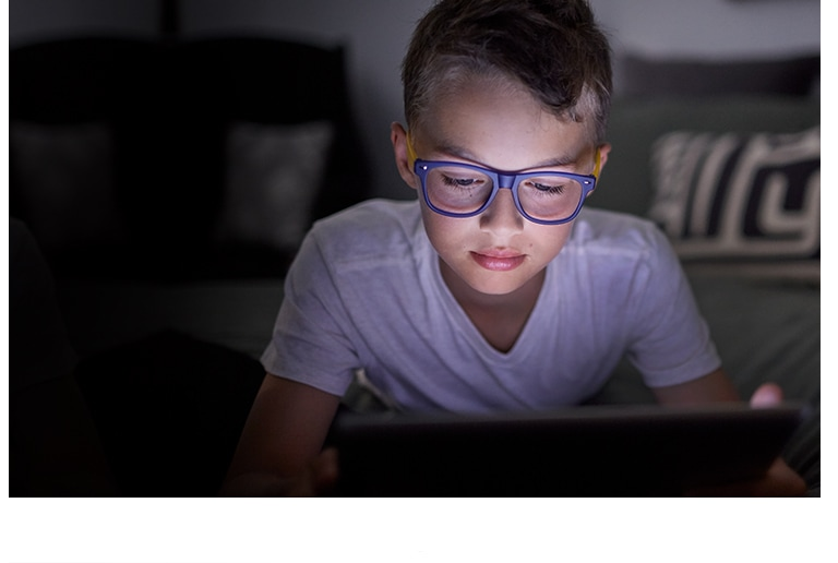 Young boy wearing Zenni Blokz Blue Blocking glasses, using a tablet.