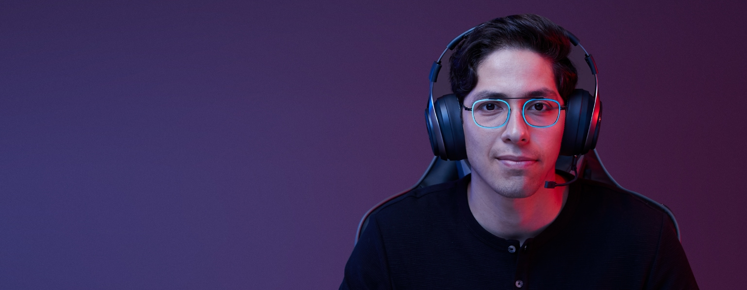 Gamer guy with short brown hair wearing bridgeless rectangle glasses #7818116 with teal metallic rims, gaming headset, and black Henley shirt.