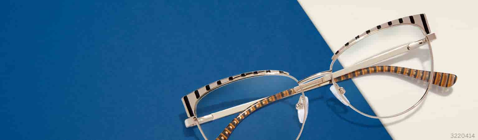 Gold metal cat-eye glasses #3220414 with etched black stripes on the brow against a blue-and-white background.
