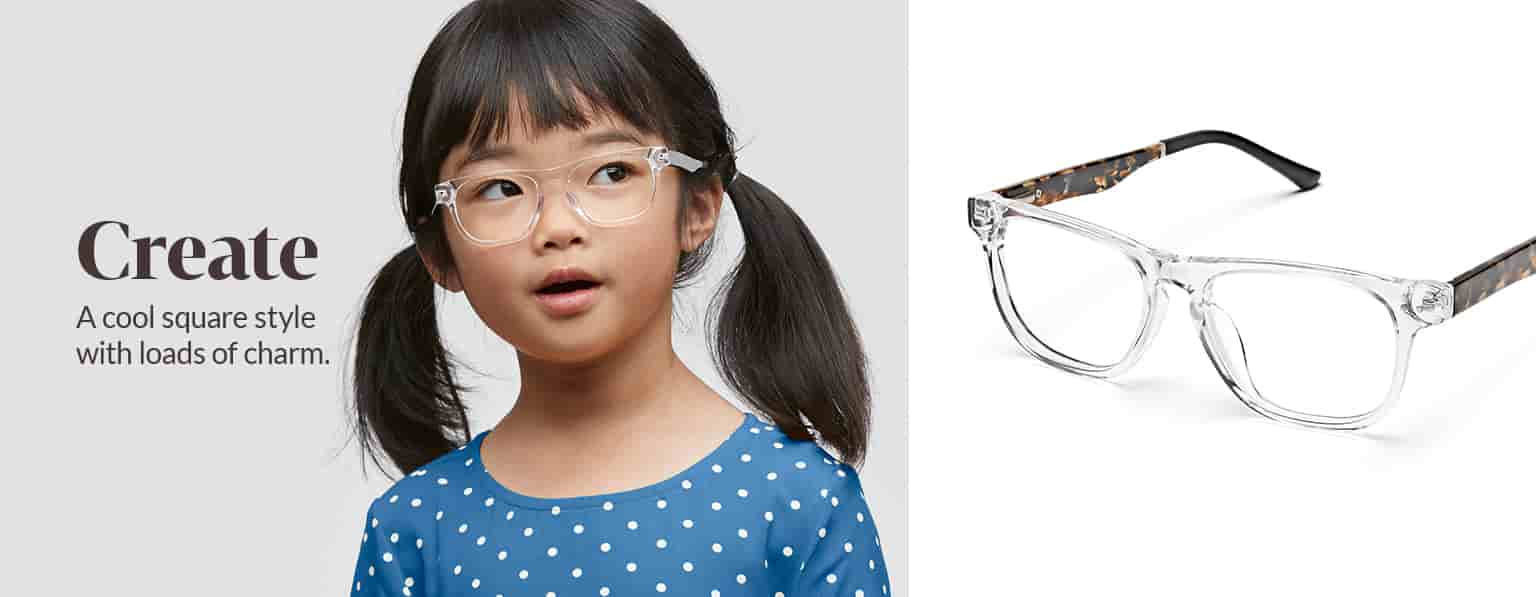 Young girl with dark brown hair in pigtails wears clear Create square glasses #4441123 and a blue shirt with white polka dots.
