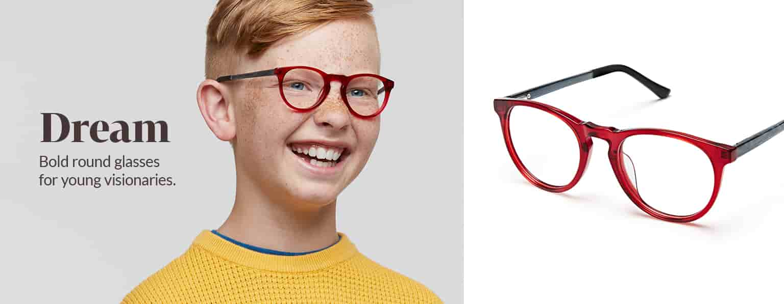 Boy with red hair and freckles wears red Dream round glasses #4441518 and a yellow waffle-knit sweatshirt.