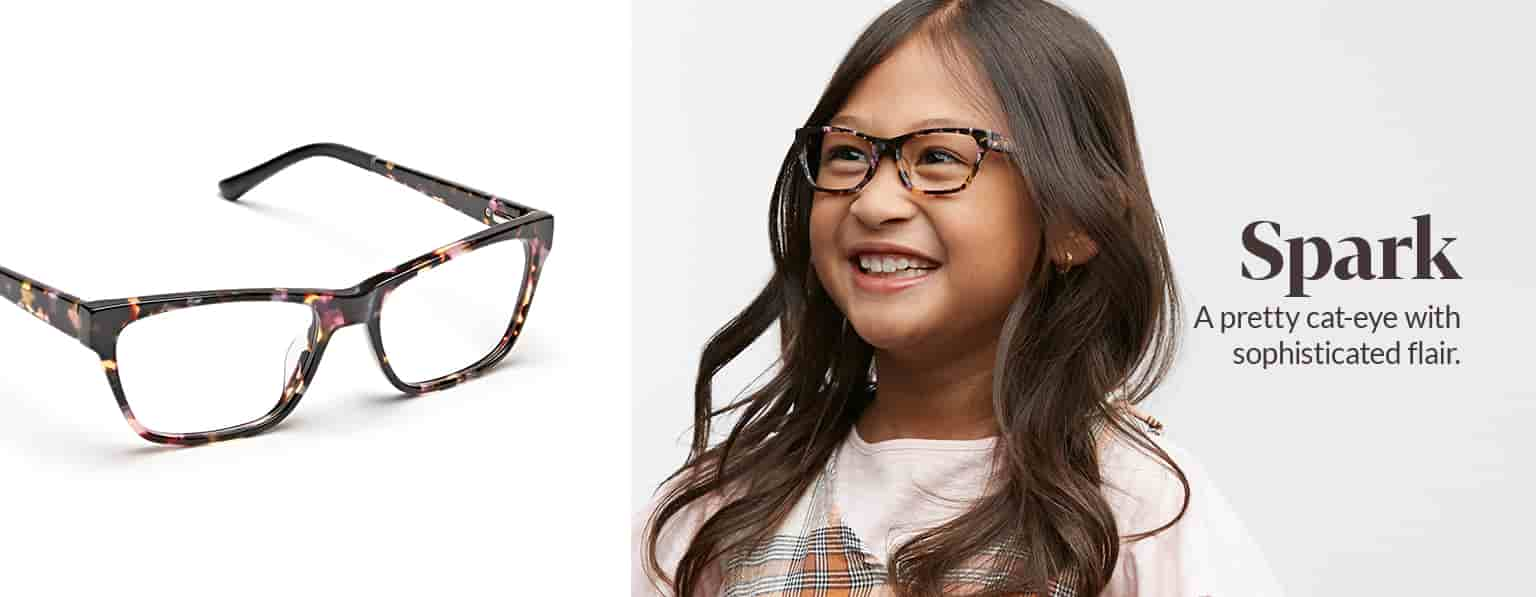 Young girl with long brown hair wears tortoiseshell Spark cat-eye glasses #4440225 with plaid jumper over a pink tee.