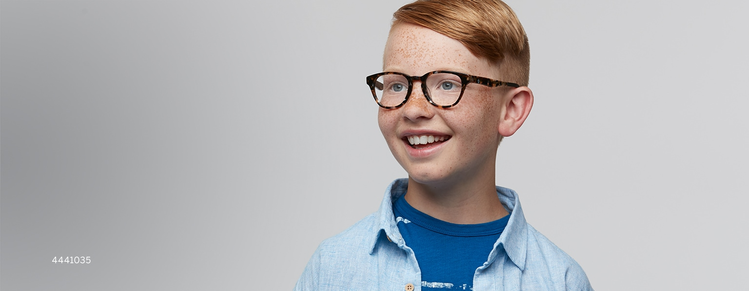 Boy with red hair and freckles wears Explore tortoiseshell round glasses #4441035 with light blue button-down shirt over a dark blue t-shirt.