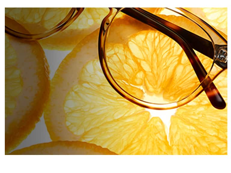 Striking clear round glasses #4431225 with opaque tortoiseshell outline on top of an orange slice.