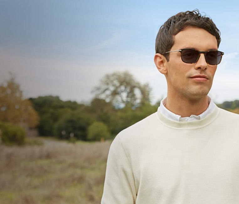 Man with short brown hair stands outside with trees in the background wearing rectangle glasses #7814225 in tortoiseshell with Blokz Photochromic lenses and an off-white sweater over a white collar shirt.