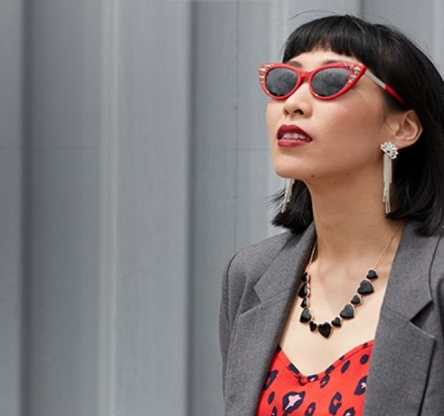 Woman with edgy black bob and red lipstick wears extreme red cat-eyes with silver studs #7820918 with dark gray Blokz tinted lenses and a gray blazer over a red leopard-print top.