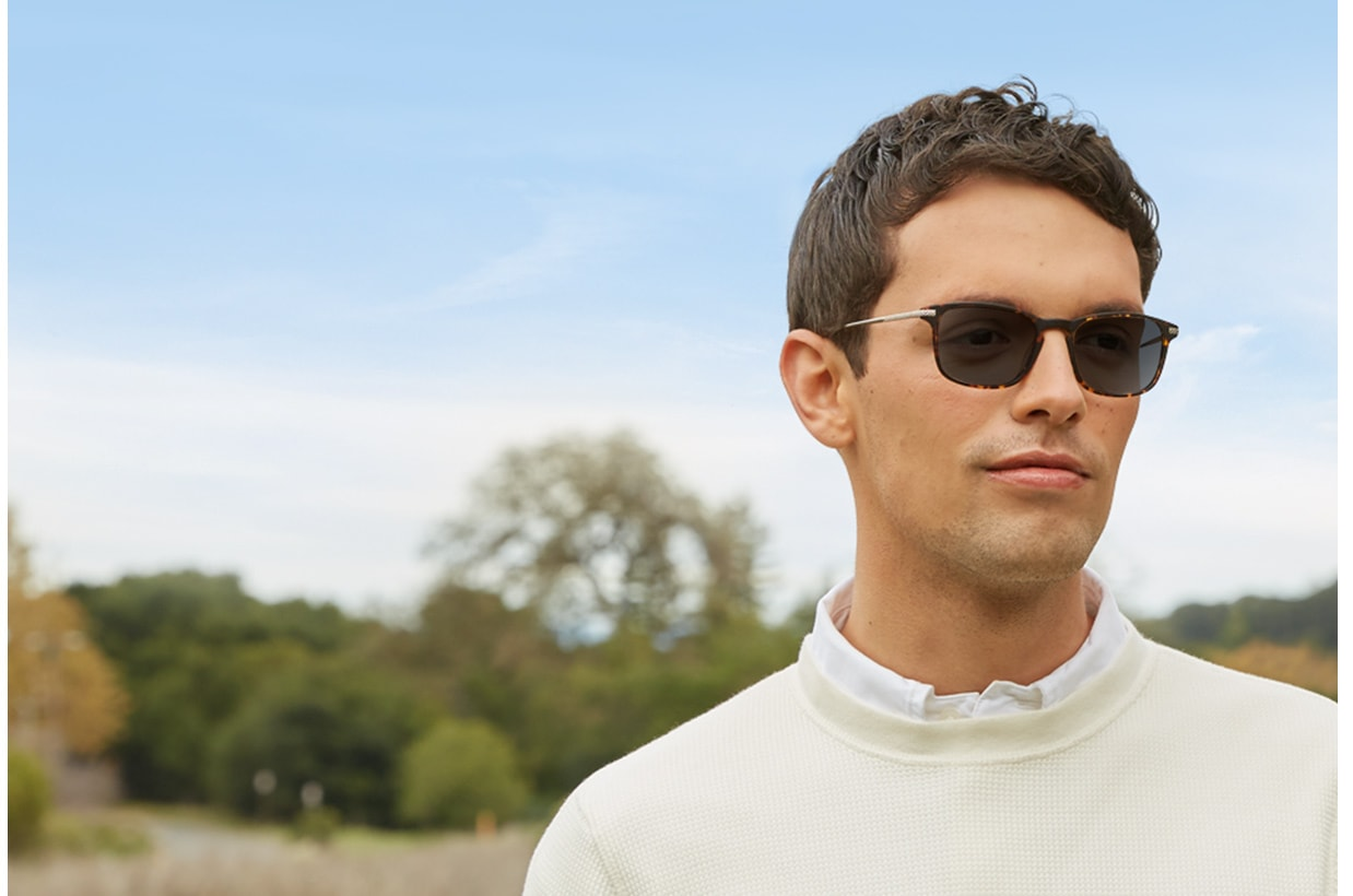 Man with short brown hair, wearing Blokz photochromic sunglasses and an off-white sweater over a white button-up shirt, stands outside with trees and blue sky in the background.