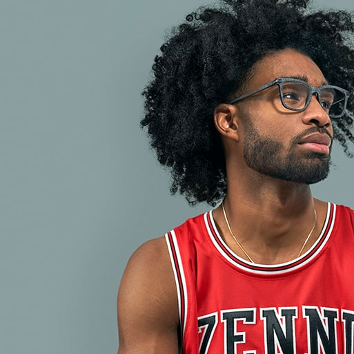 Coby White in a red Zenni basketball jersey, wearing Zenni square glasses #2026616, against a gray background.