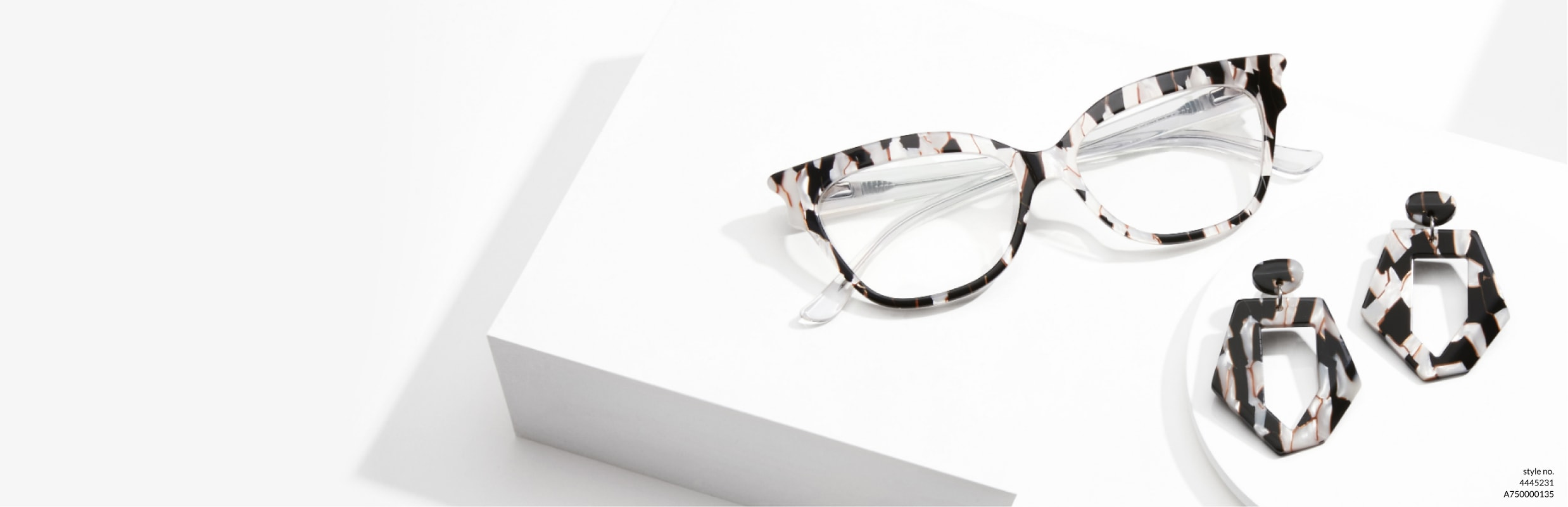 Geometric looks maximize your style. Image of Zenni cat-eye glasses #4445231 and earrings #A750000135 on a white platform.