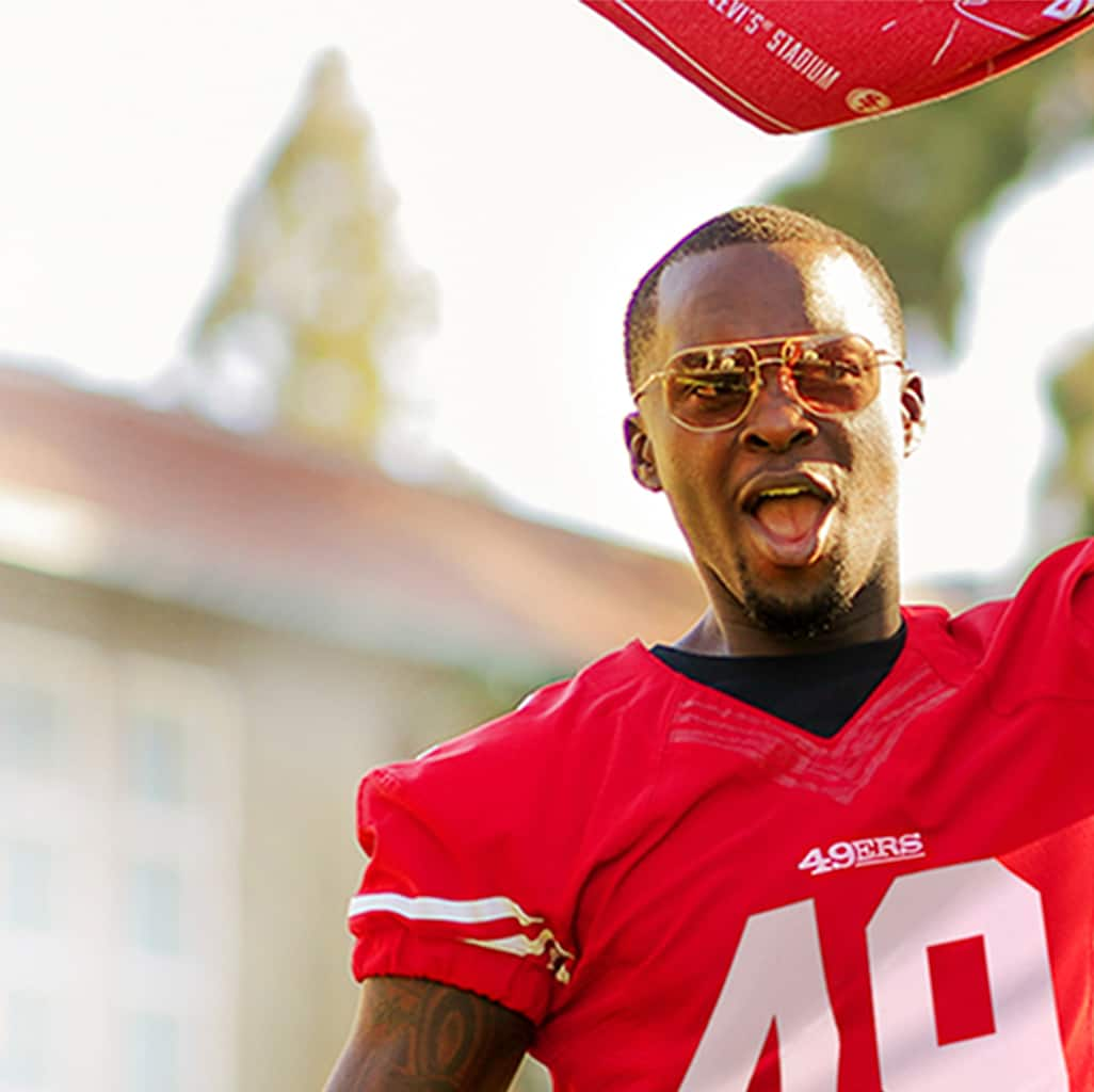 Image of a man wearing Zenni presidio aviator glasses #1127814, outside, waving a 49ers flag.