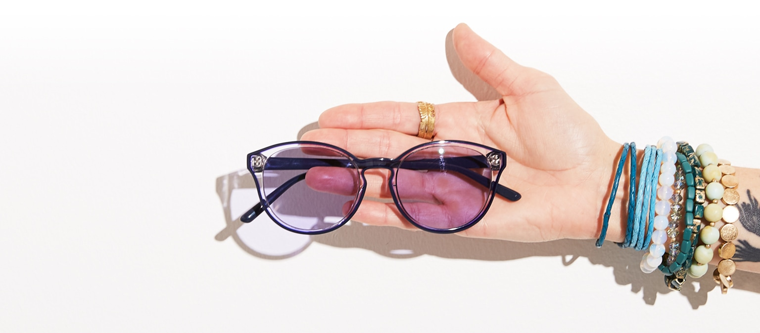 89201a633b Woman s arm adorned with bracelets and tattoo sticks out with translucent  glasses  4431117 with purple