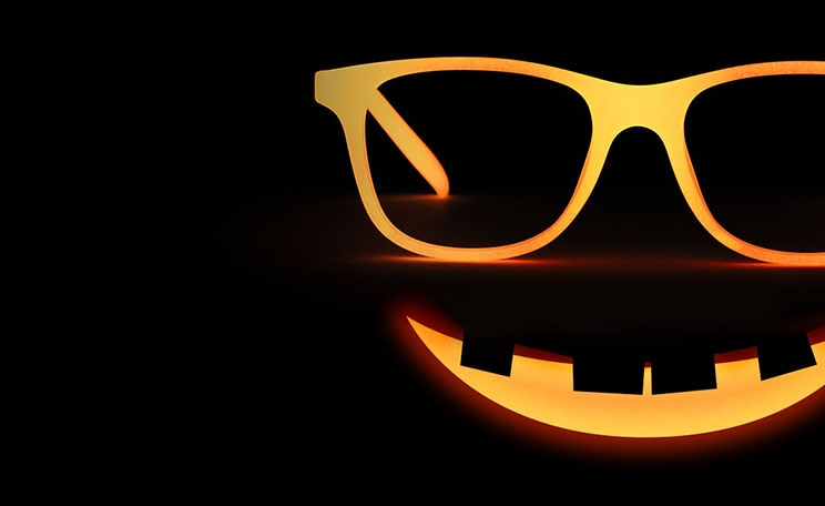 Image of Zenni kids' glow-in-the-dark square glasses #8110619, glowing orange in the dark, above a smiling expression like a jack-o-lantern.