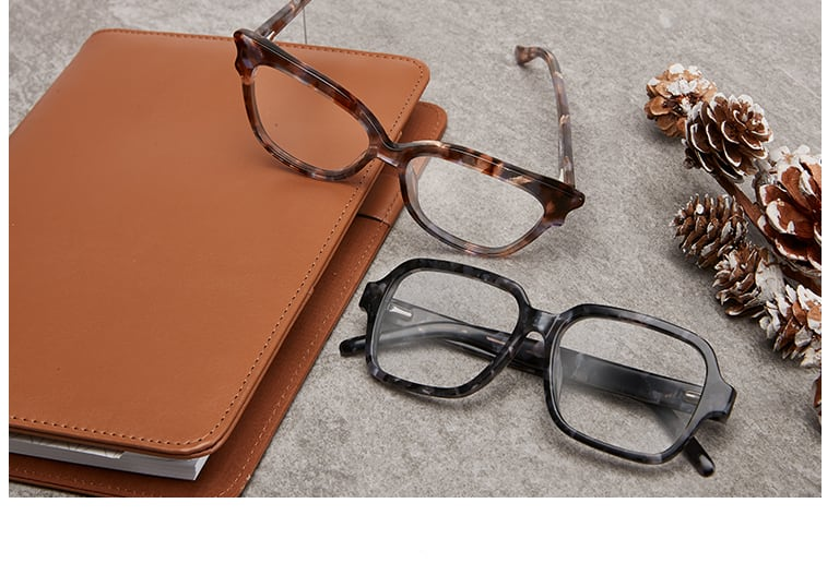 Brown-patterned acetate cat-eye glasses # 4445215 and extended fit acetate square glasses # 4444339 in granite next to a brown leather portfolio and pine cones.