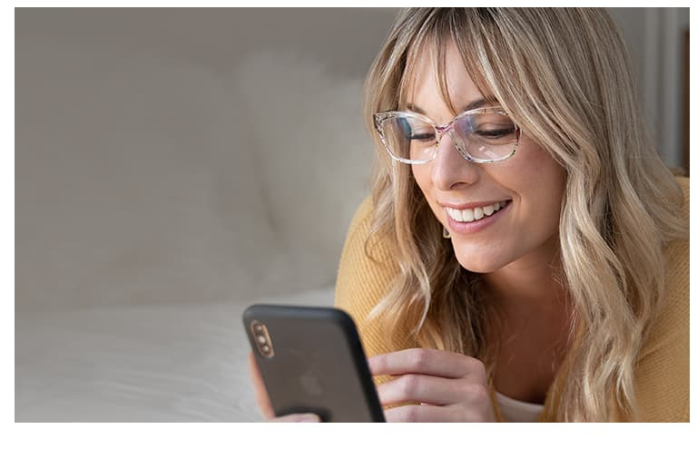 Woman with blond hair uses her iPhone while wearing translucent floral cat-eye glasses # 2018723.