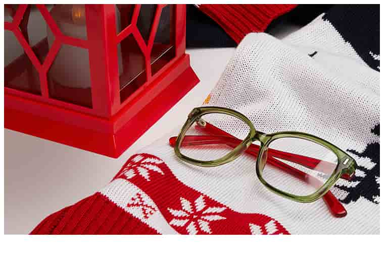 Translucent green square glasses with red temple arms #126224 on top of knit scarf with winter motif next to red lantern.