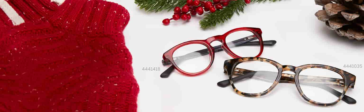 Dream kids' round glasses #4441418 in red and Explore kids' round glasses #4441035 in tortoiseshell from the Style Squad collection next to red sweater, pinecones and pine branch.