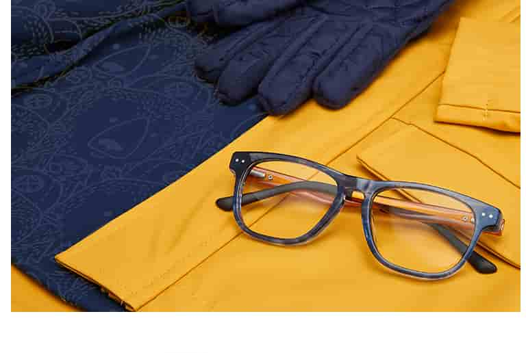 'Create' square glasses for kids #4441116 in ocean from the Style Squad collection on top of a yellow rain slicker.