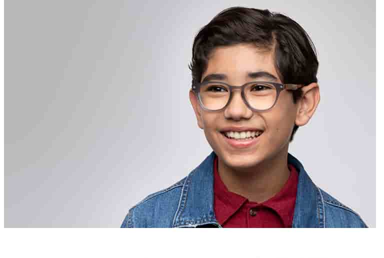 Young boy with brown hair wears gray 'explore' round glasses from Zenni's Style Squad collection for kids.