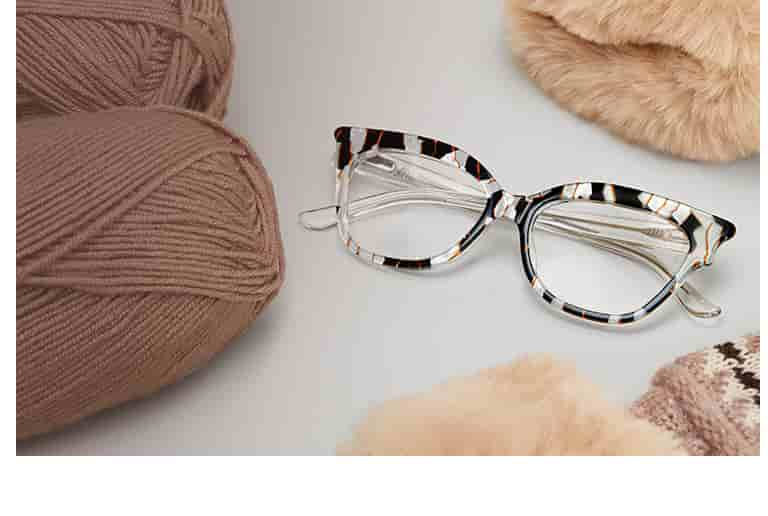 Bold cat-eye glasses #4445231 in black tortoiseshell next to balls of yard and faux fur.