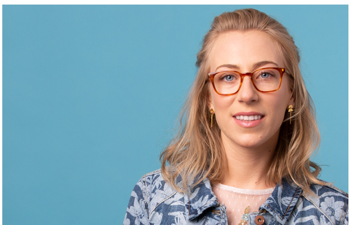 Woman in blue and white floral shirt with blond hair wearing amber square glasses #4429315.