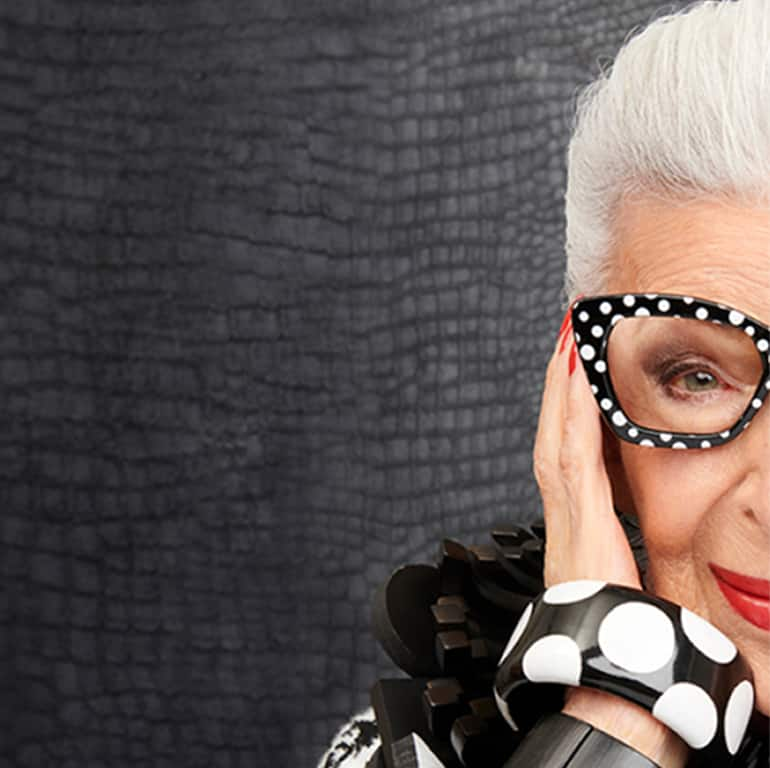 Image of Iris Apfel wearing Zenni black and white cat-eye glasses #2033421 against a black textured background.