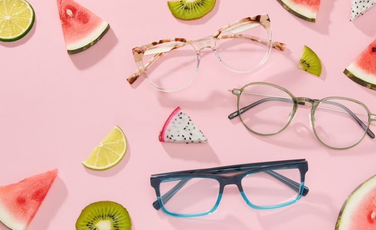 Zenni rectangle glasses #44338424 in teal, round glasses #7822624 in green, and cat-eye glasses #7823039 in clear, on a pink background with cut segments of dragon fruit, kiwi, lime, and watermelon.