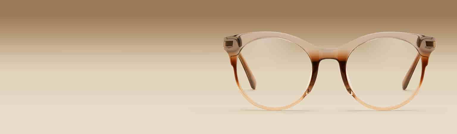 Round glasses in brown ombre #7823412 on a brown gradient background.