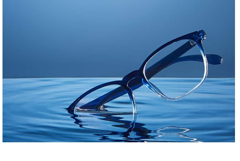 Square glasses #2020116 in navy ombre dipping into a pool of blue water against a blue background.