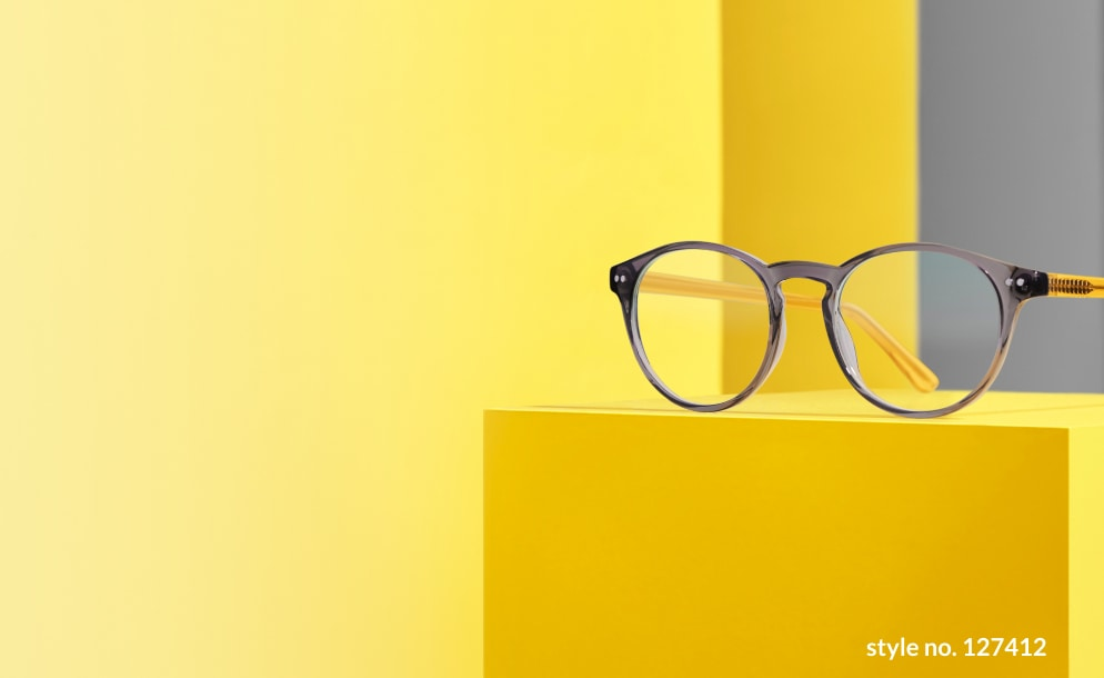 Image of a pair of Zenni round glasses #127412 on a yellow platform, against a yellow and grey background.