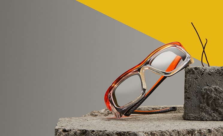 Image of Zenni safety glasses #749618 on a concrete slab, on a gray and yellow background.