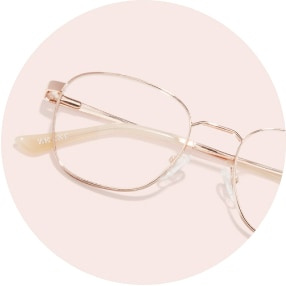 Image of a pair of rose gold metal square glasses against a light pink background.