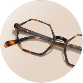 Image of a pair of tortoiseshell geometric glasses against a beige background.