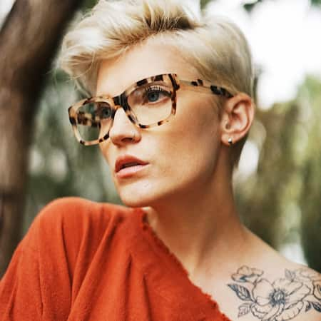 Alissa Laderer wearing Zenni Alamere square glasses #4413825 surrounded by a nature scene.