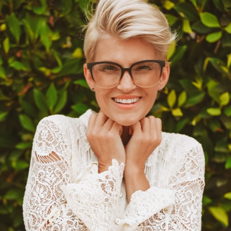 Alissa Laderer wearing zenni cat-eye glasses #2019115 in front of a tall green bush.