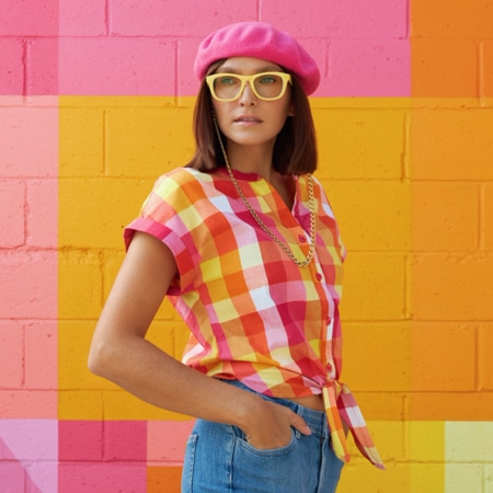 Ania Boniecka wearing Zenni square glasses #124122 against a brick wall painted in a variety of bright colors.