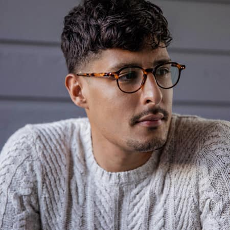 Carlos Roberto wearing Zenni Escape round glasses #4430925 in front of a grey wall background.