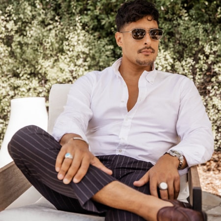 Carlos Roberto wearing zenni premium aviator sunglasses #1120112 sitting in a lounge chair outside.
