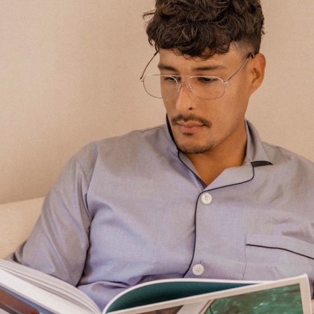 Carlos Roberto wearing zenni aviator glasses #418911 inside while reading a book.