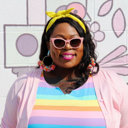 Jeannette 'Jae' Burchfield wearing Zenni Soiree cat-eye glasses #4433219 against a brick wall with artwork painted on it.