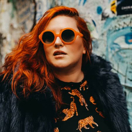 Jessy Parr wearing Zenni Pico round sunglasses #4422225 in front of a piece of colorful artwork.