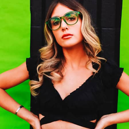 Kalianna Carpenter wearing Zenni round glasses #206024 in front of a black and green background.