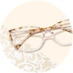 Zenni cat-eye glasses #7823039 on a cream-colored background with white floral print accents.