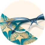 Zenni cat-eye glasses #187616 on a cream-colored background with gold fan-patterned accents.