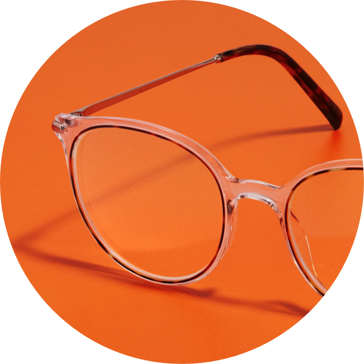 Zenni round glasses #7818623  in clear, against an orange background.