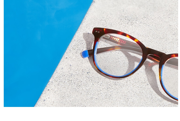 Round acetate tortoiseshell glasses with blue accented rims on a concrete slab.