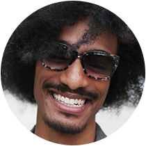 Man with black afro and goatee wears black-and-translucent patterned acetate Alamere glasses # 4413831 with gradient gray tint from the North Coast Collection.